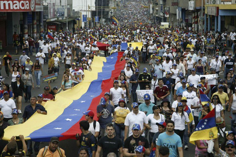Opposition supporters hold a national a flag during a rally against Nicolas Maduro's government in San Cristobal March 22, 2014. Two Venezuelans died from gunshot wounds during protests against Maduro, witnesses and local media said on Saturday, pushing the death toll from almost two months of anti-government protests to 33. REUTERS/Carlos Eduardo Ramirez (VENEZUELA - Tags: POLITICS CIVIL UNREST) ORG XMIT: VEN103