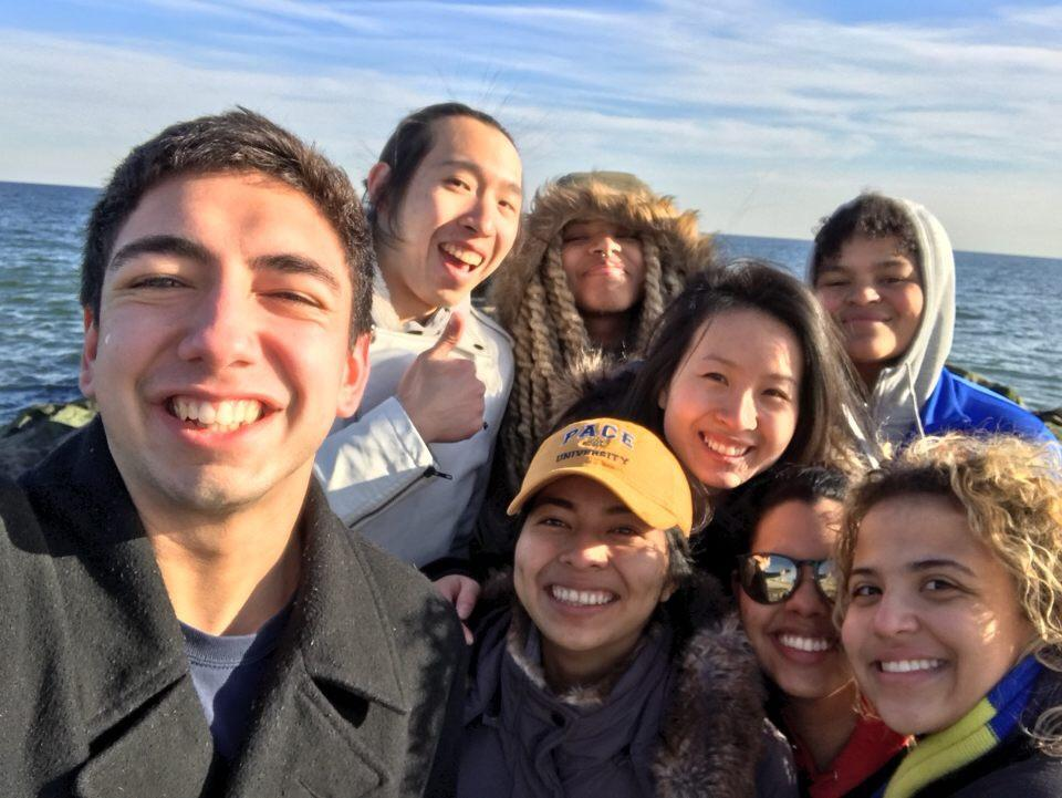 Volunteers from the University pose in front of Rockaway Beach, Queens. Courtesy of CCAR NYC.